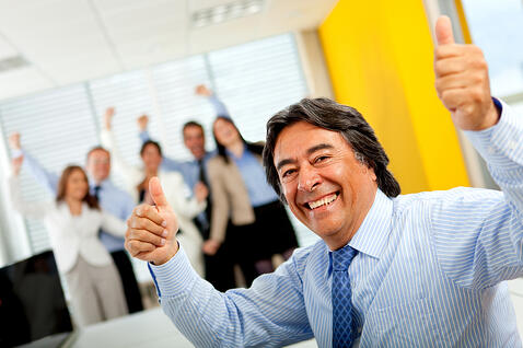 Happy man with thumbs-up leading a successful business team